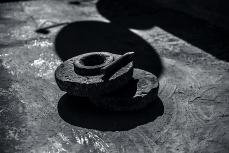 Close up of hand grinding stone or hand grinder or old motor or pestle or grain mills on rough surface still used in some of the villages of Asia and India.