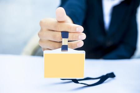 Gros plan d'un homme d'affaires portant un costume de couleur bleue et montrant sa carte d'identité isolée sur blanc.