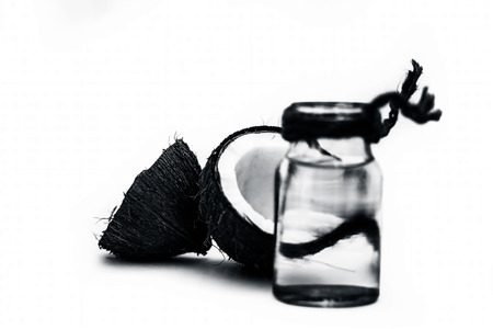 Raw organic coconut with its extracted fresh water in a white transparent glass bottle isolated on white.