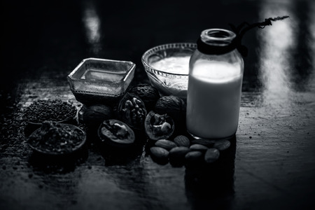 Close up of face mask or face pack of walnut along with flax seed or alsi, almonds,yogurt and milk in a glass bowl   entire raw ingredients on wooden surface.;