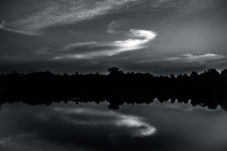 Dusk time shot of sunset through a lake with trees and clouds. Imagens