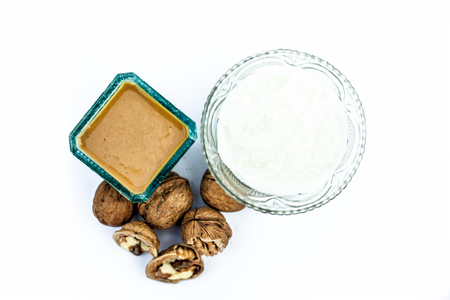 Close up of walnut face pack to prevent hair damage isolated on white i.e. walnut powder well mixed with curd in a glass bowl with entire raw ingredients.