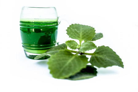 Close up of herbal organic fresh extracted Ajwain juice or Bishops weed juice isolated on white in a transparent glass with raw ajwain or ajowan. Drinking juice helps to reduce weight and detoxify.