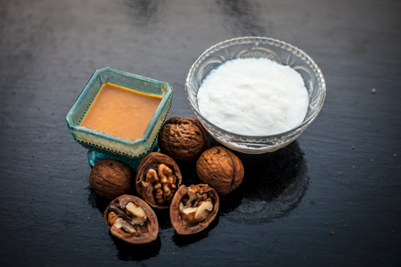 Close up of walnut face pack to prevent hair damage on wooden surface i.e. walnut powder well mixed with curd in a glass bowl with entire raw ingredients.