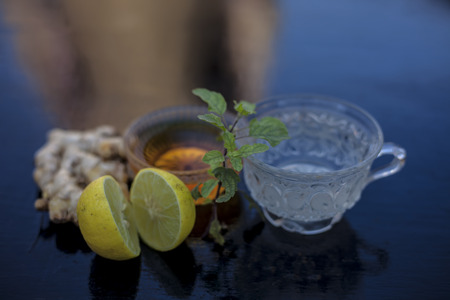 Close up of herbal green tea consisting of whiskey, ginger,honey,water,lemon and mint in a transparent cup on wooden surface.