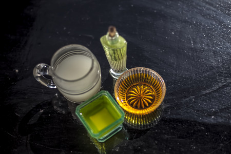 Close up of best home remedy for hair growth or to boost hair growth i.e. Chaas or buttermilk well mixed with olive oil and honey in a bowl with entire ingredients on wooden surface.