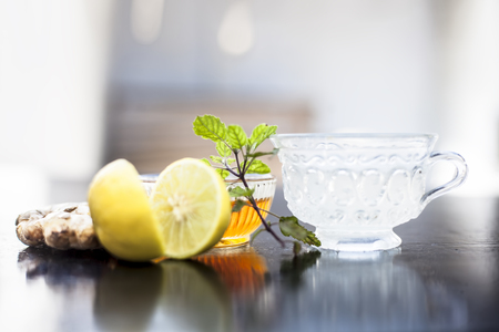 Close up of honey tea isolated on wooden surface i.e. Honey,lemon juice, water, ginger and some mint leaves all mixed together in a transparent glass cup.