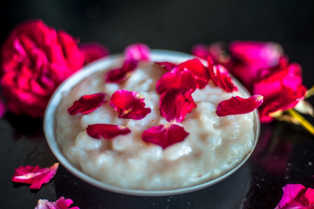 Popular Indian & Asian Ramadan dish or Ramazan dessert i.e Kheer in a glass plate along with some rose flowers and petals on it. Imagens