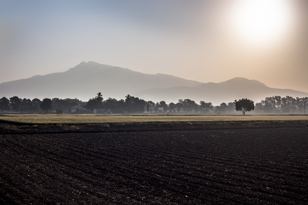 Wide landscape shot of sunrise through mountains in the early morning through fields with mist and fog.