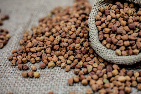 Close up shot of chickpea or chana or gram or Cicer arietinum in a gunny bag on a brown colored background.