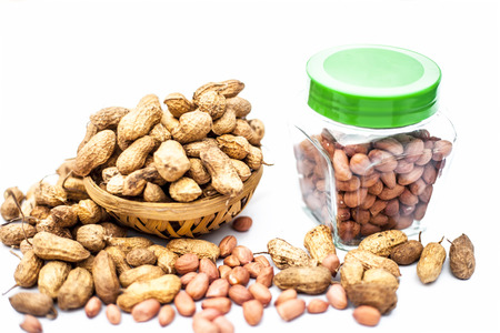 Close up of raw peanuts or groundnut isolated on white with some peeled in a separate bottle. Stock fotó