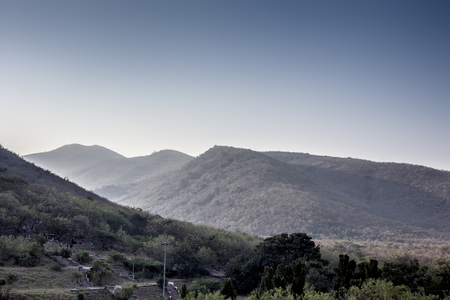 Landscape shot or view of mountains in the early morning with sunlight and flair over it.