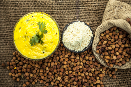 Close up of popular Indian & Asian lunch dish on brown colored surface i.e. Kadhi or Karhi  and kichdi with raw cickpeas and besan. Stock Photo