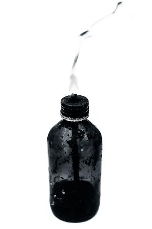 Close up of a bottle shaped kerosene lamp or oil lantern isolated on white burning.