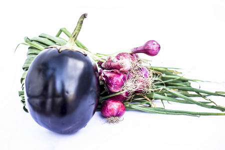 Close up of eggplant and fresh spring onion isolated on white.