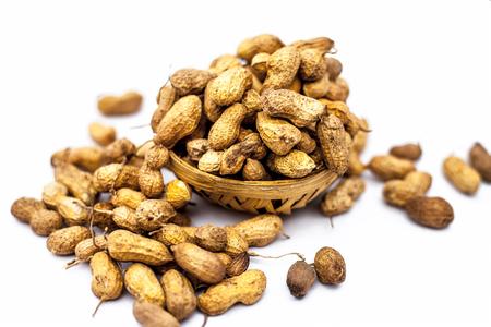 Nahaufnahme eines braun gefärbten Korbs mit Erdnüssen oder Erdnüssen oder Moongaphalee oder Arachis Hypogaea oder Goober oder Affennuss einzeln auf Weiß.