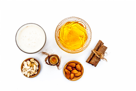 Close up of popular Indian & Asian winter drink isolated on white i.e Honey milk or shahad ka dudh in a transparent glass with entire ingredients which are milk,honey, and dry fruits.
