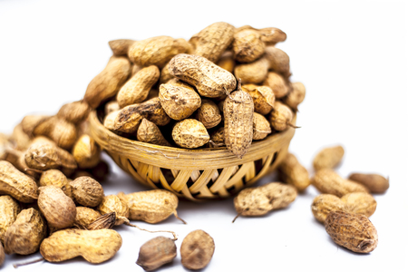 Close up of brown colored hamper having groundnuts or peanuts or moongaphalee or Arachis hypogaea or goober or monkey nut isolated on white. Stock fotó