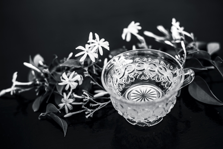 Close up of tea of Indian jasmine flower or juhi or Jasminum Auriculatum on wooden surface  in a glass cup with raw flowers.