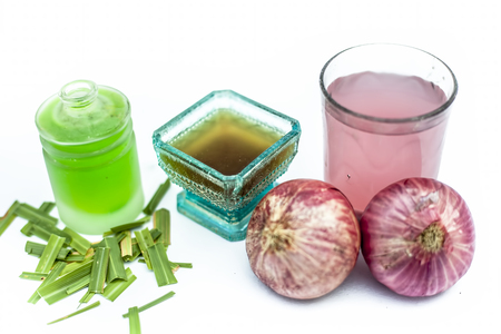 Close up of natural therapy for nourishing and strengthening hair isolated i.e. onion juice well mixed with tea tree oil in a glass bowl with entire raw ingredients in different vessels.