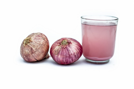 Close up of fresh organic herbal extracted Onion juice in a glass with raw onions or Allium cepa isolated on white.