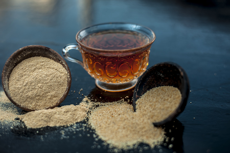 Clay bowl on wooden surface full of Poppy seeds or khus or opium poppy or bread seed poppy with its extracted herbal and organic plus beneficial detoxifying drink or tea in a transparent glass cup.