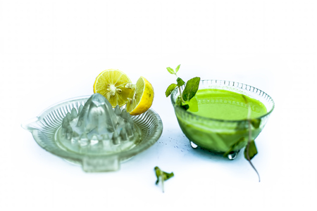 Best home remedy ingredients  to reduce acne and pimples isolated consisting of mint leaves and lemon juice in a glass bowl with entire raw ingredients in different containers isolated on white.