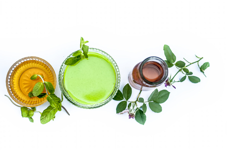 Mint or mentha or phudina face pack isolated on white i.e. mint leaves paste well mixed with rose water and honey in glass bowl with entire raw ingredients for removing acne,pimples and glows it.