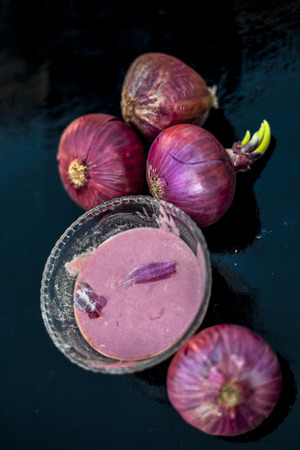 Close up of glass bowl full of extracted onion pulp in it and raw onions or pyaaj or Allium cepa.