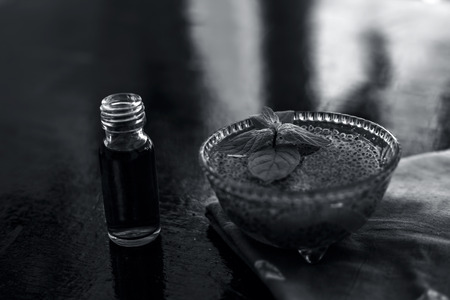 Glass bowl full of soaked sabja seeds or falooda seeds or sweet basil seeds with its extracted essence or essential oil in a transparent glass bottle on wooden surface.