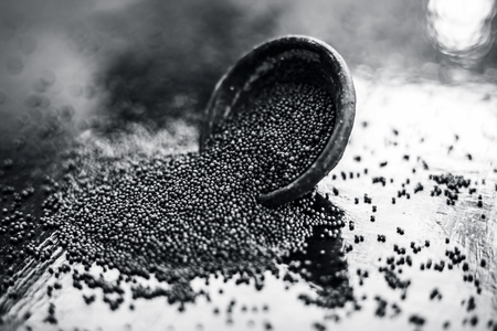 Raw organic herbal spice Mustard seeds or sarso or rai or Brassica nigra, in a clay bowl on wooden surface.