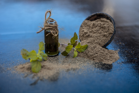 Brahmi di erbe ayurvediche o Waterhyssop con la sua essenza in una piccola bottiglia di vetro trasparente insieme alla sua polvere su una superficie di legno.