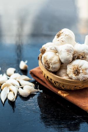 Raw organic garlic bulbs or lasun or Allium sativum in a hamper or basket on wooden surface.
