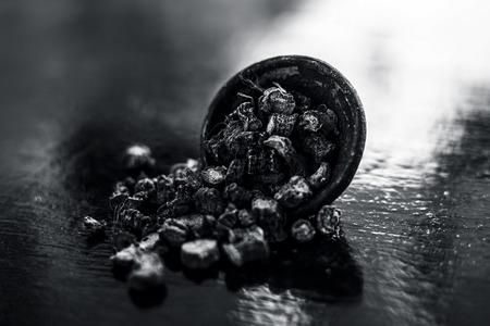 Popular Indian & Asian ayurvedic organic herb musli or Chlorophytum borivilianum or Curculigo orchioides or kali moosli in a clay on wooden surface.