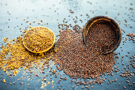 Raw organic herbal spice Mustard seeds or sarso or rai or Brassica nigra, in a clay bowl along with its powder in another bowl on wooden surface. Stockfoto
