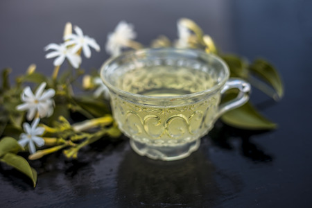 Close up of tea of Indian jasmine flower or juhi or Jasminum Auriculatum on wooden surface  in a glass cup with raw flowers. Reklamní fotografie - 123032288