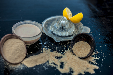 Key ingredients to make poppy seeds cake with lemon juice or muffins or dough nuts on wooden surface i.e. Poppy seeds and its powder and some lemon juice in glass juicer.