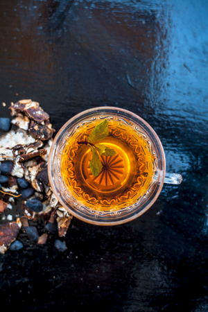 Tamarind or imli or amli in a clay bowl along with its roasted seeds and extract tea in a transparent glass cup with mint or mentha leaves on top on wooden surface. Stock Photo