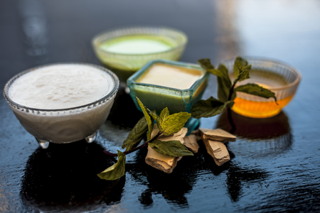 Best face pack or ubtan to remove excess oil from skin on wooden surface consisting of mentha leaves or mint leaves along with fullers earth or bleaching clay and curd with honey.
