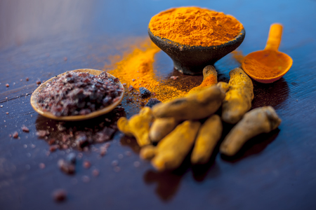 Close up of clay bowl full of turmeric powder along with some raw turmeric and black salt in another bowls on shiny surface.