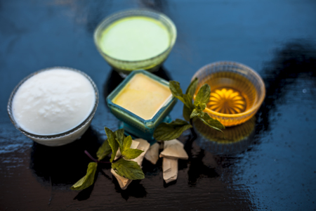 Best face pack or ubtan to remove excess oil from skin on wooden surface consisting of mentha leaves or mint leaves along with fuller's earth or bleaching clay and curd with honey.