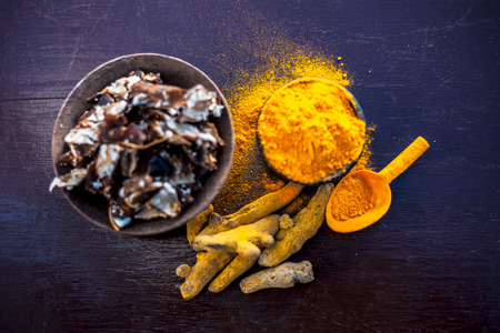 Tamarind or imli or amli in a clay bowl along with its roasted seeds on wooden surface with turmeric or haldi in a clay bowl used for treating acne and pimple. 写真素材