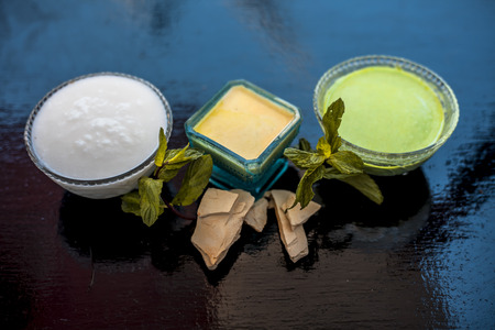 Face pack of fullers earth or mud of multan or bleaching clay on wooden surface along with curd and mint leaves. This face pack is used to nourish,hydrates cleans skin.