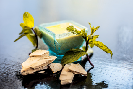 Fullers earth or mulpani mitti or multani mitti or bleaching clay well mixed in a blue colored glass bowl along with some mint leaves for decoration on it and raw clay also on wooden surface. Stok Fotoğraf