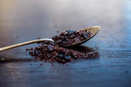 Raw organic rock salt or sendha namak or kala namak in a golden spoon on wooden surface.
