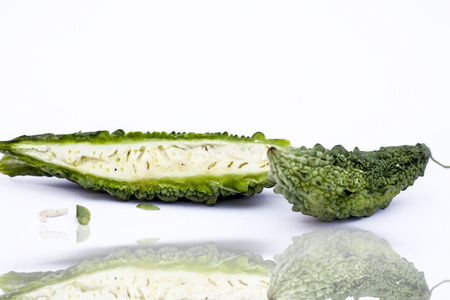 Raw organic bitter melon or Bitter Cucumber or Bitter Gourd isolated on white with its reflection.