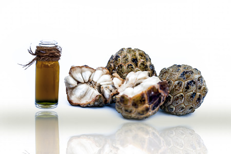 Raw organic fresh fruit Custard apple or sugar apple or sweetsop with its oil in a transparent glass bottle isolated on white along with its reflection.;
