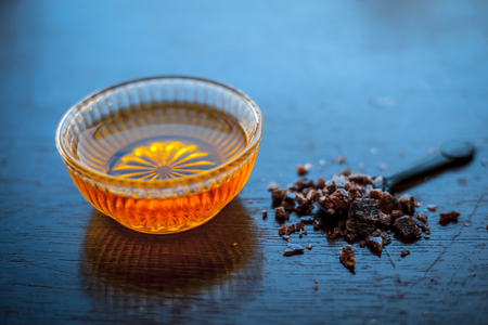 Close up of raw honey in a glass bowl on wooden surface along with powdered rock slat in a black colored spoon.Helps in getting good possible sleep. Stock Photo