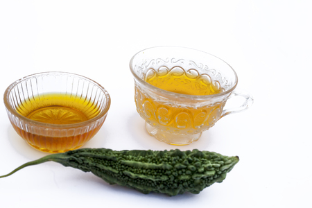 Popular detoxifying herbal tea isolated on white i.e. Bitter melon or Bitter cucumber tea isolated along with honey and its ingredients.