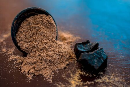 Raw organic hing or devils dung or Asafoetida on wooden surface along with its powder in a black colored clay bowl and some mint leaves or mentha leaves on it. Stock fotó